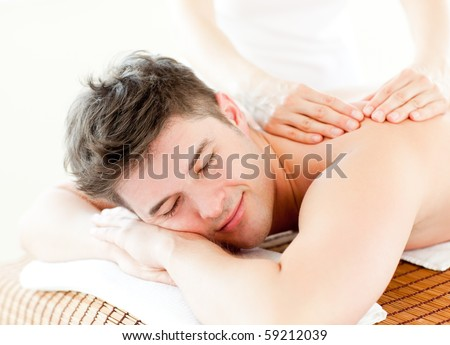 Relaxed young man receiving a back massage in a spa center - stock photo