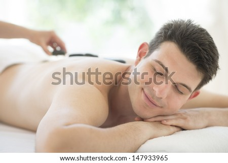 Relaxed young man receiving hot stone therapy at health spa - stock photo