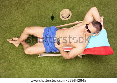 Relaxed young man sitting on a sun lounger and listening to music on his cell phone in his backyard - stock photo