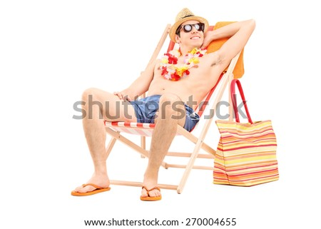Relaxed young man sitting shirtless in a sun lounger chair and looking in the distance isolated on white background - stock photo
