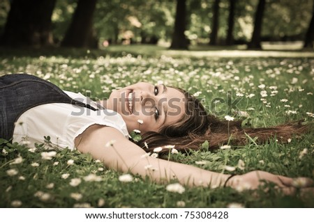 Relaxed young person (teenage girl) lying in grass and flowers with stretched hand - closed eyes - stock photo