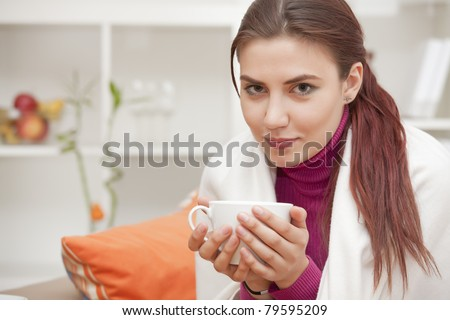 relaxed young woman at home with cup tea in her hands - stock photo