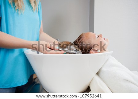 Relaxed young woman getting her washed before haircut at beauty salon