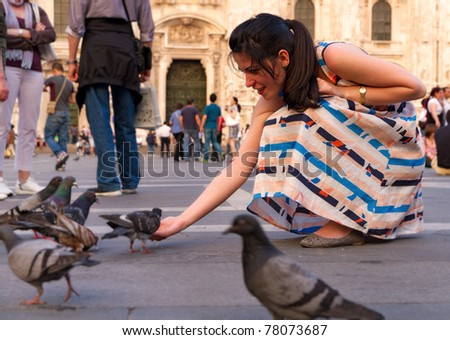 relaxed young woman in colorful dress feeds the pigeon on lively square in front of Dome of Milano - stock photo