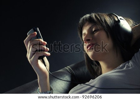Relaxed young woman lying on sofa while listening music in headphones
