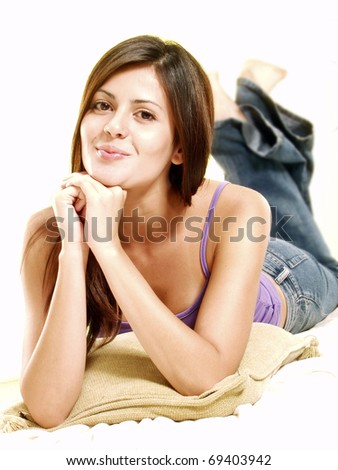 Relaxed young woman on white over a cushion. - stock photo