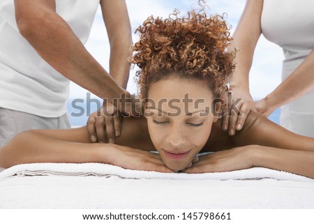 Relaxed young woman receiving shoulder massage from massagers at spa - stock photo