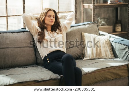 Relaxed young woman sitting in loft apartment - stock photo