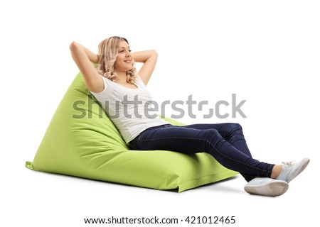 Relaxed young woman sitting on a comfortable green beanbag isolated on white background - stock photo