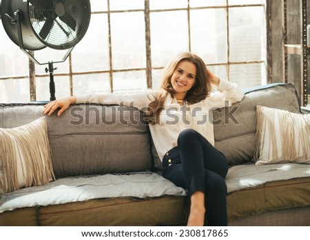 Relaxed young woman sitting on couch in loft apartment - stock photo