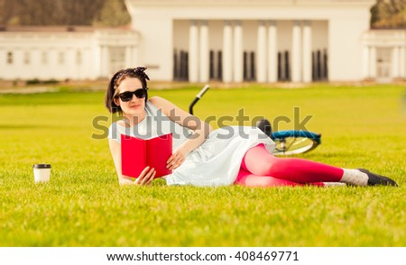 Relaxed young woman standing outside and reading in the city park and enjoying a coffee - stock photo
