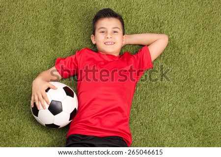 Relaxed youngster in a red football jersey lying on a pitch, holding a football in his hand and looking at the camera - stock photo