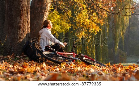 Relaxes woman cyclist with bike sits among fallen leaves autumn morning in nature illuminated by the bright rays of the rising sun and enjoy recreation - stock photo