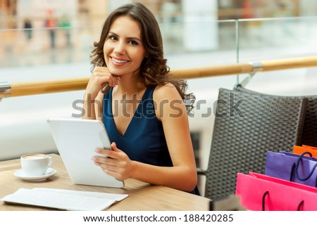 Relaxing after day shopping. Beautiful woman enjoying a cup of coffee after shopping - stock photo