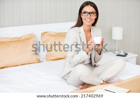 Relaxing after hard working day. Beautiful young smiling businesswoman in suit drinking coffee and looking away while sitting on the bed in hotel room  - stock photo
