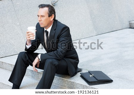 Relaxing after hard working day. Thoughtful mature man in formal wear holding coffee cup and looking away while sitting at the staircase - stock photo