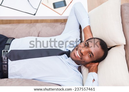 Relaxing after long day working. Top view of handsome young African man in shirt and tie holding hands behind head and smiling while lying on the couch  - stock photo