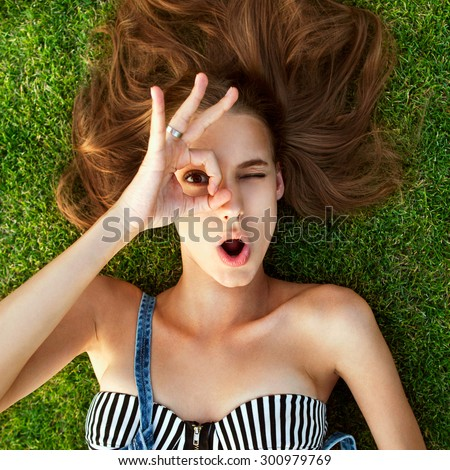 Relaxing after long trip. Top view of beautiful young woman  lying on the grass, hands shows gesture ok - stock photo