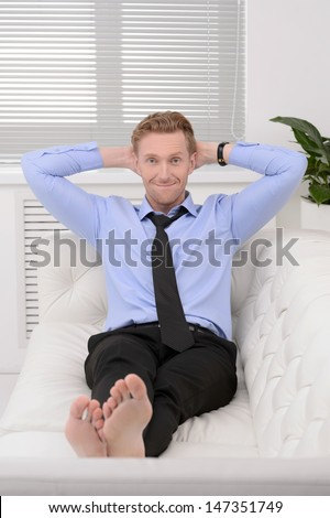 Relaxing after working day. Cheerful young businessman relaxing on the couch and holding his head in hands - stock photo