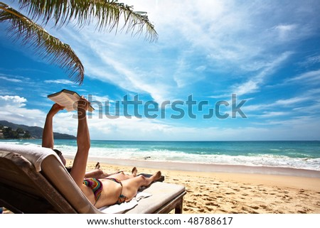 Relaxing and reading on the beach - stock photo