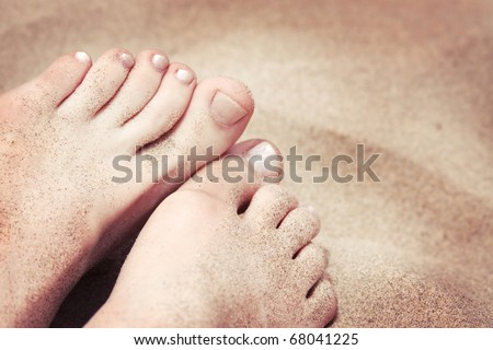 Relaxing at a beach, with your feet in the warm sand. - stock photo
