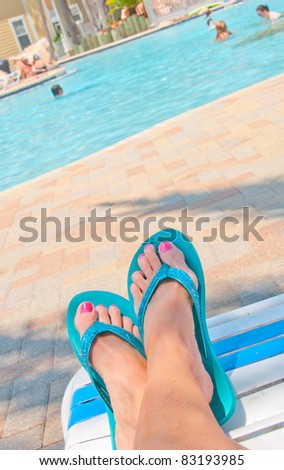 Relaxing at poolside under palm tree - stock photo