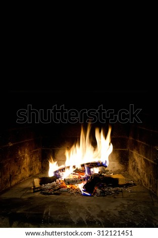 Relaxing at the fireplace on winter evening. Hearth place christmas postcard template. flaming, flames of fire. Black background. Realistic fire. Black background, copy space. - stock photo