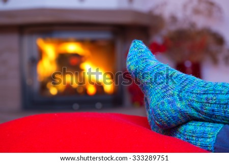 Relaxing at the fireplace on winter eveningWoman relaxes by warm fire and warming up her feet in woollen socks. Close up on feet. Winter and Christmas holidays concept. - stock photo