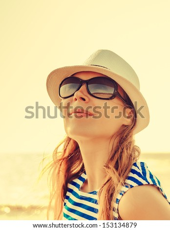 Relaxing beach woman enjoying the summer sun happy in a cap and sunglasses with face raised to the sunlight. - stock photo