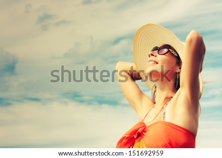 Relaxing beach woman enjoying the summer sun happy in a wide sun hat at the beach with face raised to the sunlight. - stock photo