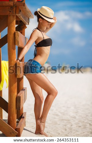 Relaxing beach woman enjoying the summer sun happy standing in sun hat at the beach. Summer. Vacation. Tropical beach - stock photo