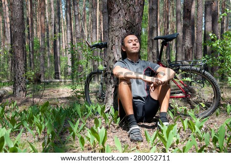 Relaxing bicyclist in coniferous forest in the spring under a large pine tree in a lily of the valley - stock photo