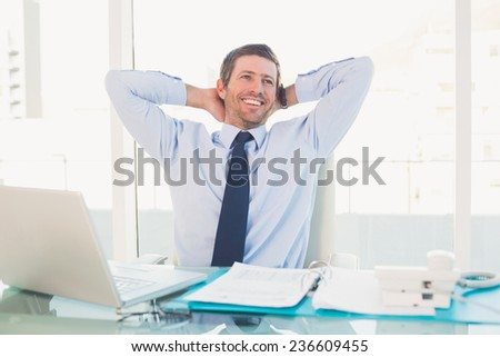 Relaxing businessman at his desk in his office - stock photo
