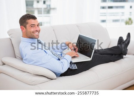 Relaxing businessman on a sofa with a laptop at home
