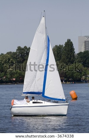Relaxing by sailing with a little pleasure yacht on a lake
