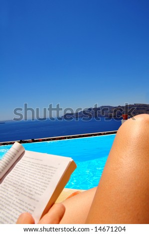 relaxing by the pool against the dramatic caldera (volcano) in famous Santorini, Greece - stock photo