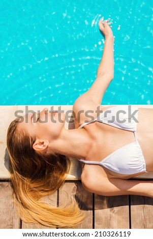 Relaxing by the pool. Top view of beautiful young woman in white bikini lying by the poolside and touching water with hand