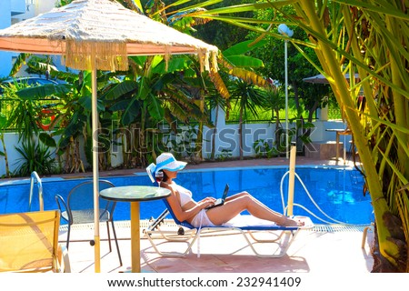 Relaxing by the pool ; Young woman relaxes by the pool with a laptop - stock photo