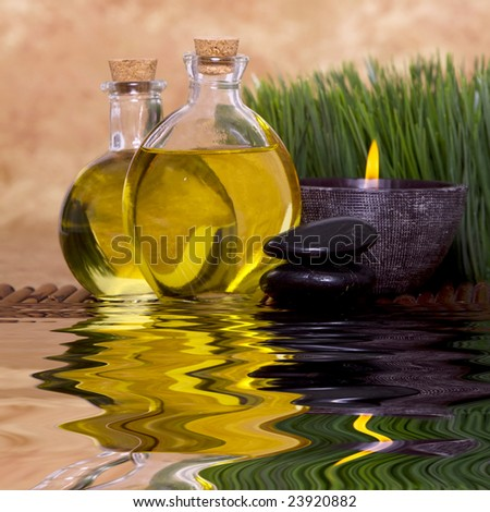 Relaxing candle and massage oil bottles front of green grass - stock photo