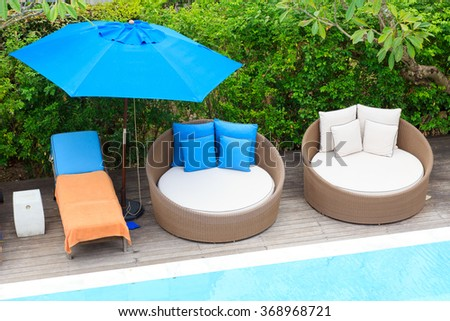 Relaxing chairs beside of swimming pool - stock photo