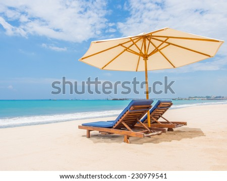 Relaxing couch chairs with parasol on white sandy Beach looking towards ocean and blue sky in Bali Indonesia - stock photo