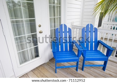 Relaxing depiction of blue Adirondack Chairs in Key West Florida with a palm tree in the background - stock photo