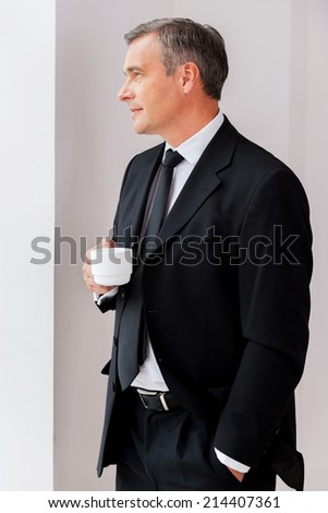 Relaxing during coffee break. Thoughtful mature man in formalwear holding coffee cup and looking away while standing near window - stock photo