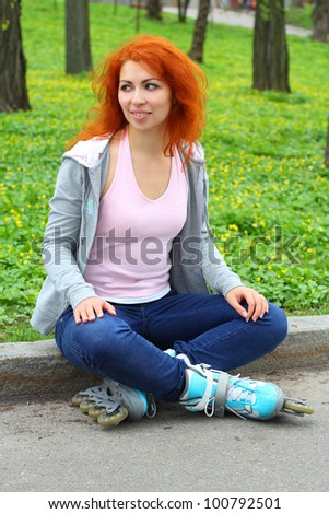 Relaxing ginger girl on skates in the park looking away - stock photo