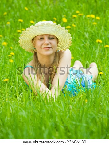 Relaxing girl in hat on meadow grass - stock photo