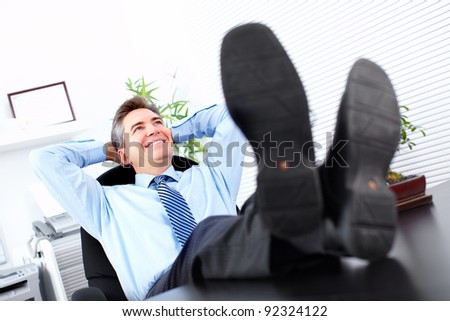 Relaxing handsome businessman. At the modern office.