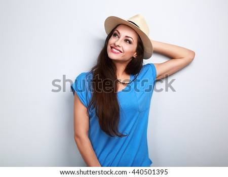 Relaxing happy smiling woman in hat thinking about summer holidays on blue background - stock photo