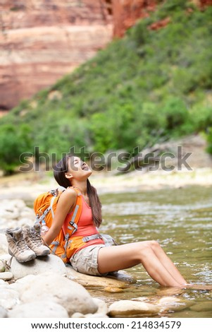 Relaxing hiker woman resting feet in river happy serene and relaxed afterhiking in Zion National Park. Female hiker in Zion Canyon wearing backpack. Healthy lifestyle multiracial Asian girl, Utah, USA - stock photo