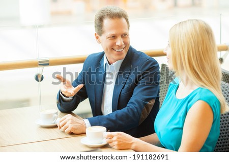 Relaxing in cafe together. Beautiful mature couple drinking coffee and talking to each other while sitting in coffee shop - stock photo