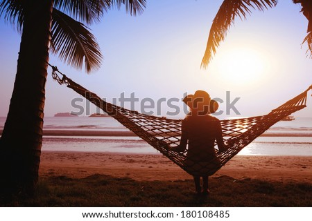 relaxing in hammock at sunset on the paradise beach - stock photo